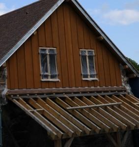 Le toit de l'appenti avant la couverture : les 3 premiers rangs de tuile sont déjà posés en partie haute.