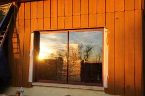 La baie vitrée... Rouge pétant sur un bardage ocre jaune... Mais le coucher de soleil, magique, transforme tout.