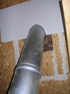 Une demi-plaque de Fermacell posée pour faire le raccord au rampant. Le trou est isolé avec de la laine de verre.
